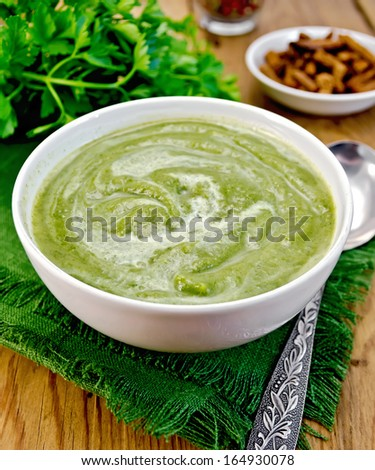 Green soup puree in a white bowl with spoon on a napkin, parsley, croutons, peppers on a wooden boards background - stock photo