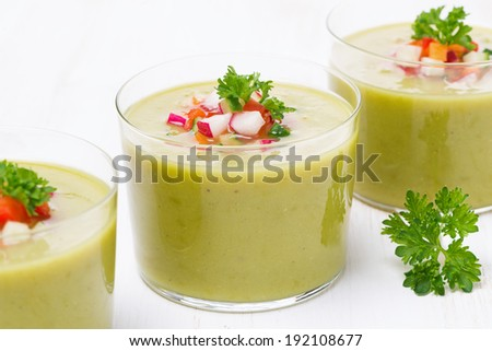 green soup with fresh vegetables in glasses, close-up