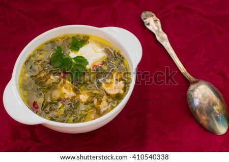 Green soup with sorrel, parsley and sour cream. Red fabric background. Top view - stock photo