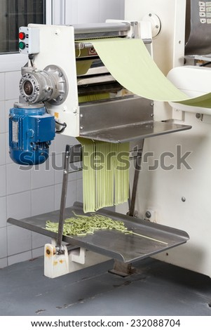 Green spaghetti pasta sheet being processed in automated machine at commercial kitchen - stock photo