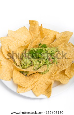 Green spicy guacamole served with corn tortilla chips over white background - stock photo
