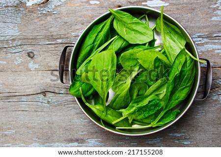 green spinach over wooden background, top view - stock photo
