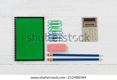 Green spiral notepad with pencils, eraser, calculator, and paper clips on desktop.