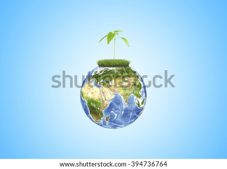 Green sprout growing in globe close-up on blue background.  Elements of this image are furnished by NASA - stock photo
