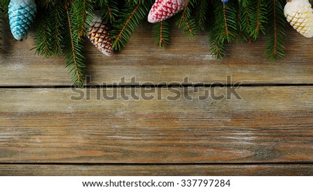 green spruce branch and xmas decorations on wooden panel - stock photo