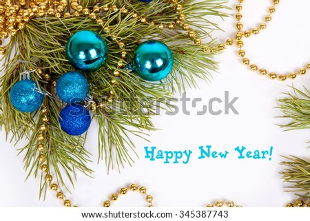 Green spruce branches, blue Christmas balls and golden beads on a white background