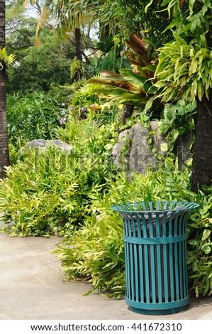 Green steel bin in public garden - stock photo