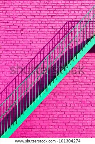 green step on original pink brick wall - stock photo