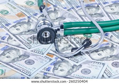 Green stethoscope 100 dollar bills, shallow depth of field - stock photo