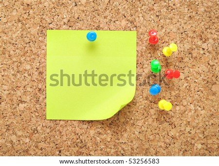 green sticky note over brown cork background - stock photo