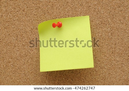 green sticky notes with push pin on cork broad
