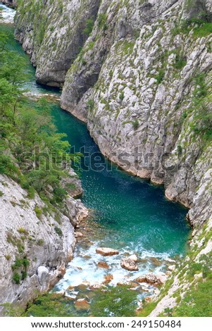 Green stream of water flowing at the bottom of a canyon - stock photo