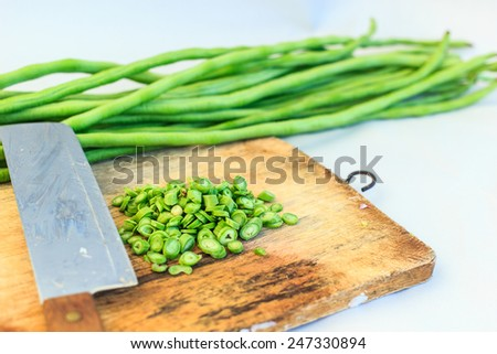 green string beans and knife closeup on wooden board - stock photo