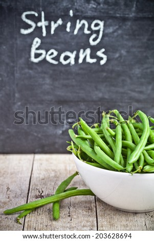 green string beans in a bowl and blackboard - stock photo