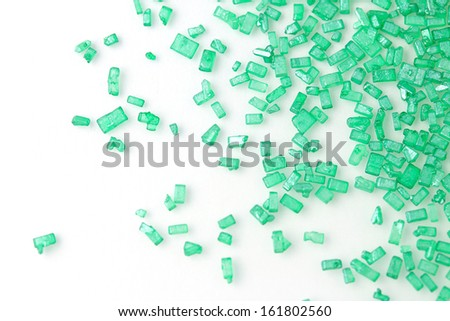 Green sugar sprinkles scattered on white - stock photo