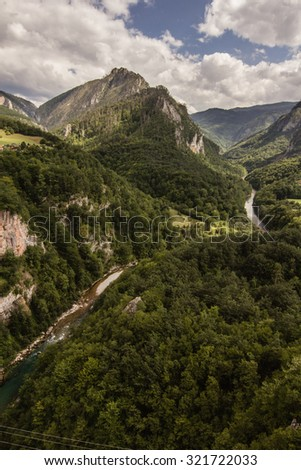 green summer mountains of world's second largest canyon of Tara river in Montenegro with white clouds on blue sky landscape