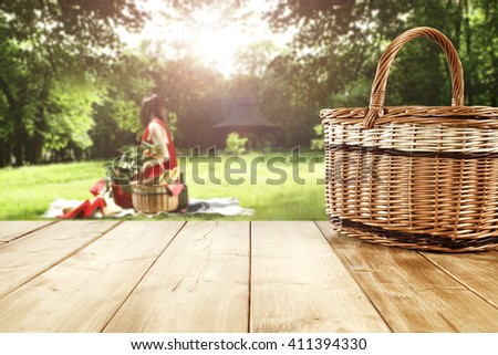 green sunny day in park and basket and yellow wooden table and leaves and trees  - stock photo