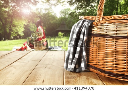 green sunny day in park and green leaves of trees and basket  - stock photo
