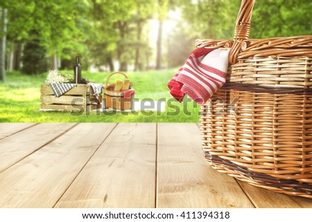 green sunny day in park and red napkin wooden table and picnic basket  - stock photo