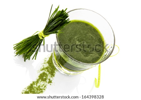 Green superfood. Green juice in glass and wheat grass isolated on green background. Healthy living. - stock photo