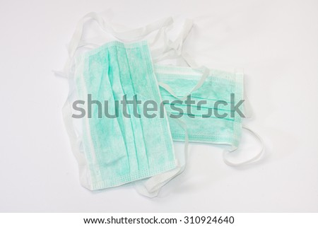 Green surgical mask on the white background. - stock photo