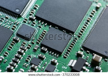 Green system board with microchips and transistors. Microchips are shown in different sizes. Macro photo.