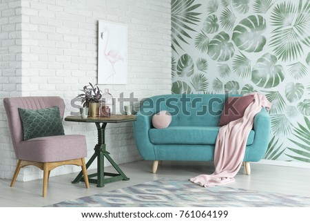 Green Table With A Plant Between Pink Chair And Blue Sofa In Floral Living  Room With