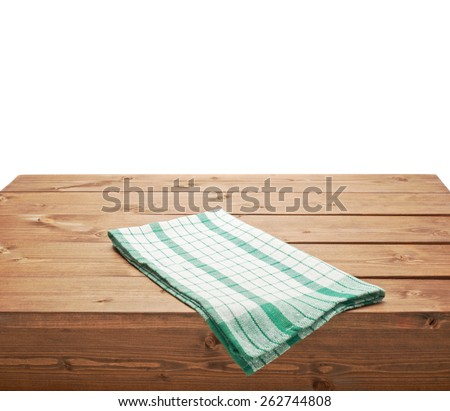 Green tablecloth or towel over the surface of a brown wooden table, composition isolated over the white background - stock photo