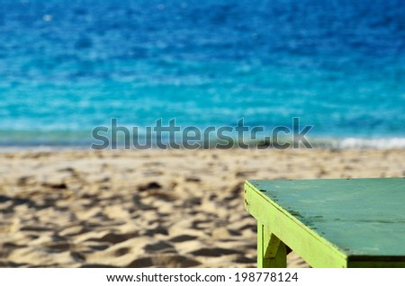 Green tables on the beach - stock photo