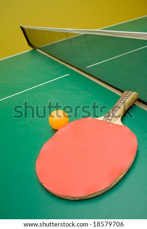 Green tabletennis table with red paddle and orange ball
