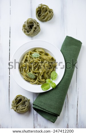 Green tagliatelle over white wooden background, above view - stock photo