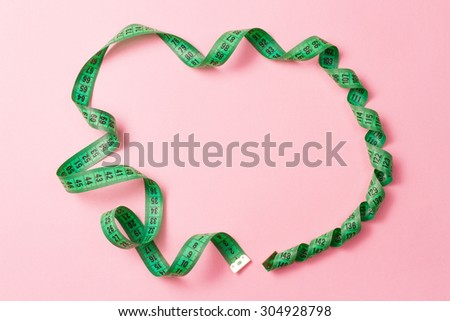 Green tailor measuring tape on pink background.  - stock photo
