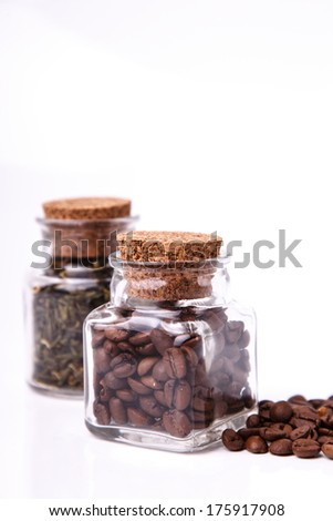 Green tea and coffee beans in two glass jars - stock photo