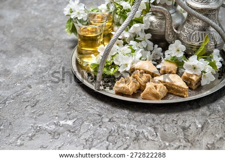Green tea and traditional sweets baklava. Oriental silver tableware. Selective focus - stock photo
