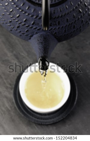 Green tea being poured out of a Japanese teapot, selective focus - stock photo