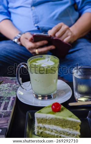 green tea cake with a a cup of hot green tea latte - stock photo