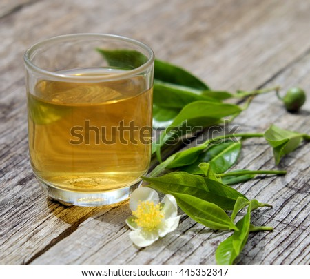 Green tea cup on wooden background with leaf and flower, green tea is good drink, healthy beverage can antioxidant, rich vitamin