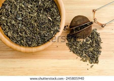 green tea, dried leaves with filter, on wooden background - stock photo