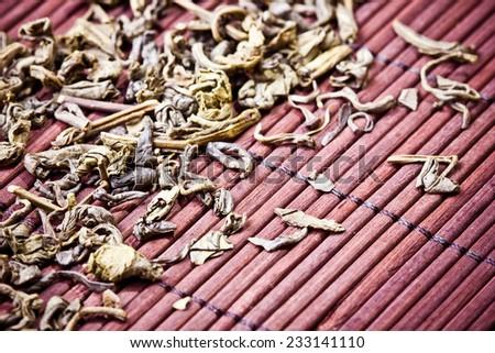 Green tea dry leafs on bamboo mat. - stock photo