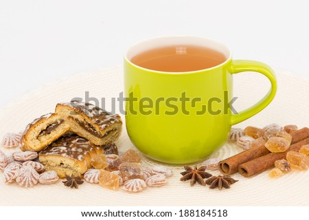 green tea in a mug and candy gingerbread cinnamon ahar fennel on a white background
