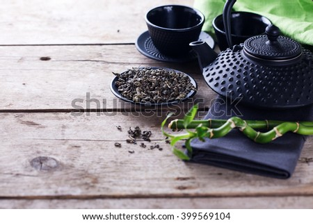 Green tea in bowl and traditional asian tea set  on aged wooden background. Selective focus is on tea. Place for text. - stock photo