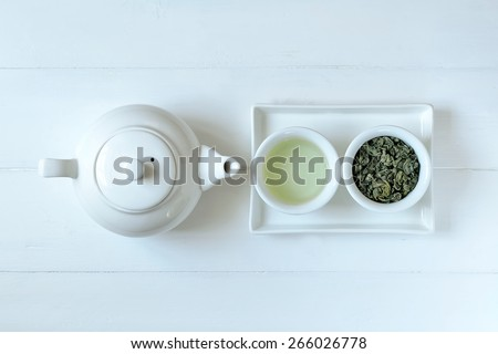 Green tea in tea pot and white cups, top view - stock photo