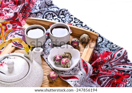 Green tea in the form of a ball with a red flower in a ceramic bowl on a wooden tray surrounded by the kettle and cups made of ceramic - stock photo