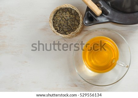 Green tea in the glass cup on the wooden background. Overhead view