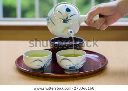 Green Tea is poured into the cup closeup - stock photo
