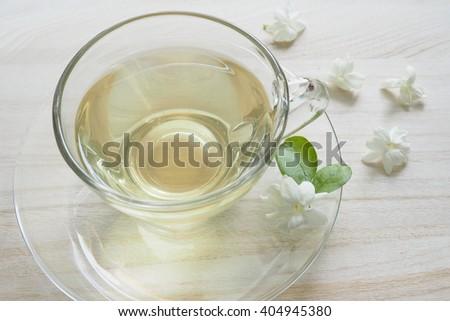green tea jasmine in cup and jasmine flower on table - stock photo