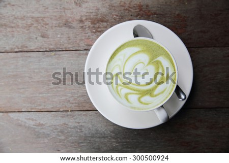 green tea latte on wood background - stock photo
