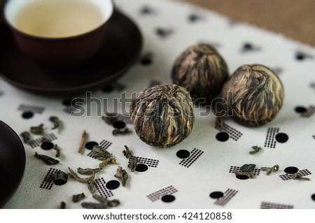Green tea leaves and small balls bundle of dried tea leaves on Japanese pattern tablecloth - stock photo
