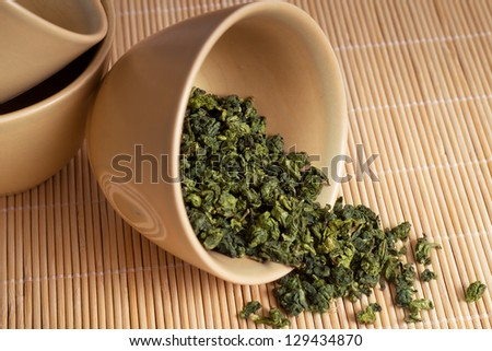 Green Tea leaves in a cup - stock photo
