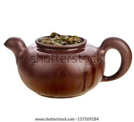Green tea leaves in clay teapot isolated on white background - stock photo